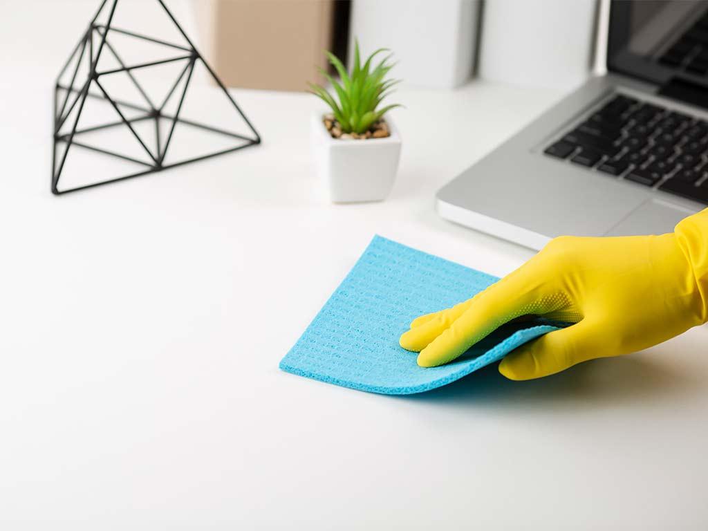 Bürotisch wird abgewischt bei der Büro Reinigung